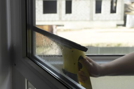 Wash the window at home with a battery wiper. The apparatus yellow collects drops of water and clean the window. Hands scrub the window. White window frame with a handle.