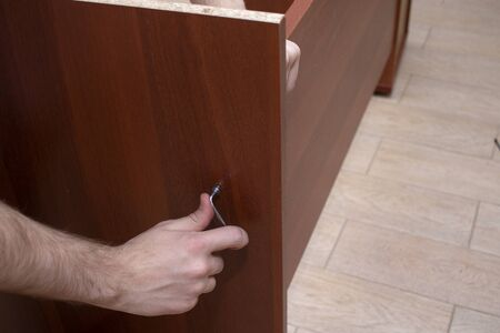 A male tool collects furniture color spanish walnut. Hands screw the furniture screw with a hexagonal wrench. 写真素材