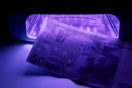 Authentication with infrared light at the detector. Paper bill in ultraviolet color. Fifty Euros 50 Euro. 写真素材
