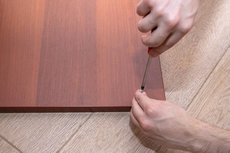 A male tool collects furniture color spanish walnut. A screwdriver screws the screws to the wooden wall of the table. 写真素材