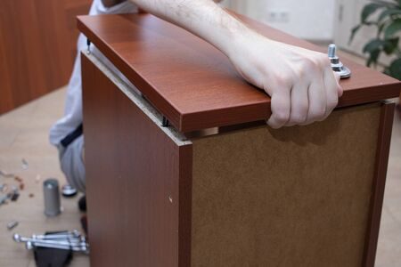 A male tool collects furniture color spanish walnut. Assembly of a desk drawer cover. Banque d'images