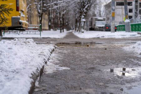 Winter road for pedestrians cleaned from snow. Chemicals pour on a pedestrian path, the snow has melted. Frost, snow fell.