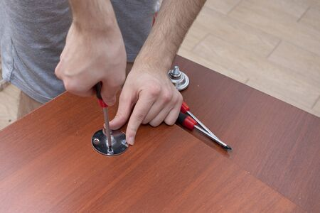 A male tool collects furniture color spanish walnut. Screwdriver screws on a steel plate, table assembly.