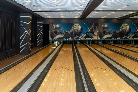 Wooden paths in a bowling game. White pins are standing.