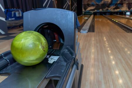 Bowling balls lie in a holder in a line. Colored balls and bowling lane. Green ball
