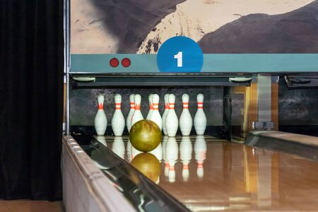 Bowling ball rolls along a wooden path to the pins. Golden ball knocks down pins. Stok Fotoğraf