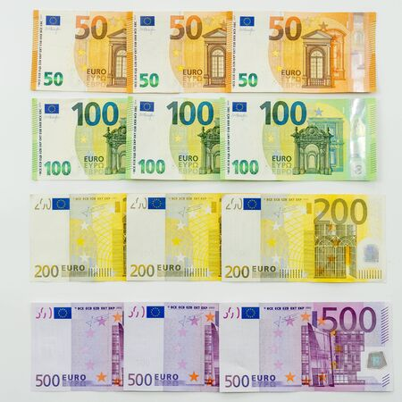 European currency lies on the table. Banknotes one hundred, two hundred, fifty, five hundred euros neatly in a row lie on the surface. Design concept, on a white background.