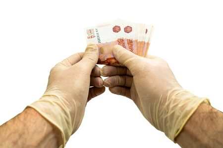 Two hands in white medical protective gloves are counting a bundle of notes with a face value of 5,000 five thousand rubles. Isolated white background. Virus protection concept.