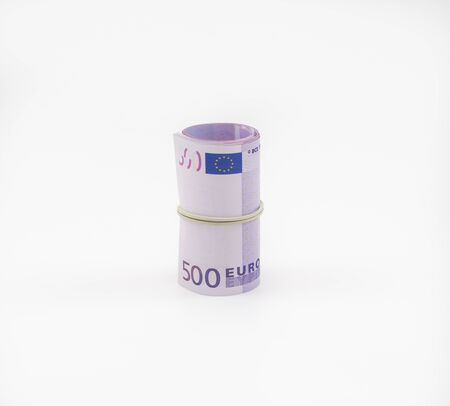 Banknotes five hundred and 500 euros in a roll with an elastic band. European currency to save. Close-up, white background. The concept of the safety of deposits and money. 写真素材