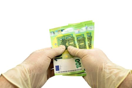 Two hands in white protective gloves hold a bundle of 100 Euro bills. Isolated white background. Virus protection concept.