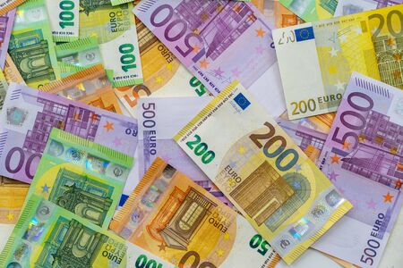 European currency lies on the table. Banknotes five hundred, one hundred, two hundred, fifty euros are scattered in a chaotic manner. Blank for design, background. Close-up. View from above.