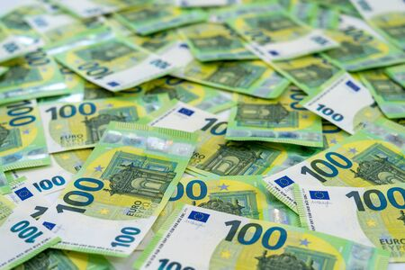 Banknotes of 100 hundred euros are scattered in a chaotic manner. European currency. Side view, close-up. Blank for design, background.