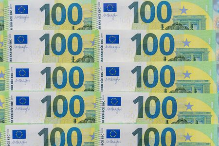 Banknotes of one hundred and 100 euros are in exactly two rows. Blank for design, background. European currency, close-up.
