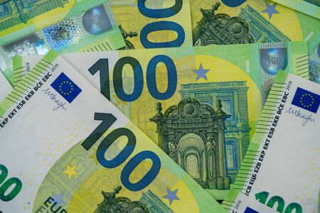 Banknotes of 100 hundred euros are scattered in a chaotic manner. European currency lies on the table. Close-up. Blank for design, background. View from above. 写真素材