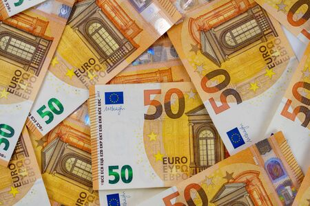 Banknotes of 50 fifty euros are scattered in a chaotic manner. European currency blank for design, background. View from above. Close-up.