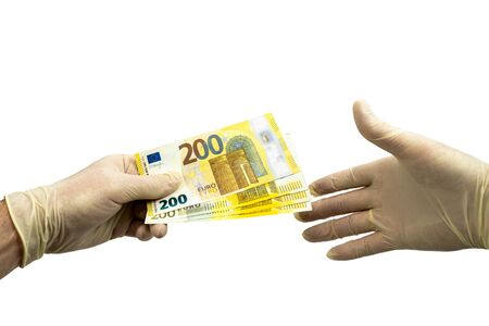 One hand in white protective gloves holds out a bundle of 200 two hundred euro bills to the other hand in a white medical glove. Isolated white background. Virus protection concept.