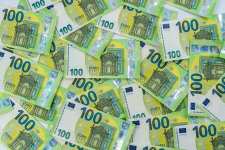Banknotes of 100 hundred euros are scattered in a chaotic manner. European currency lies on the table. Blank for design, background. View from above.