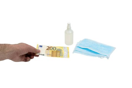 A hand buys a bill of 200 two hundred euros a few blue medical surgical masks and a bottle of antiseptic. The concept of virus protection in Europe. Isolated background.