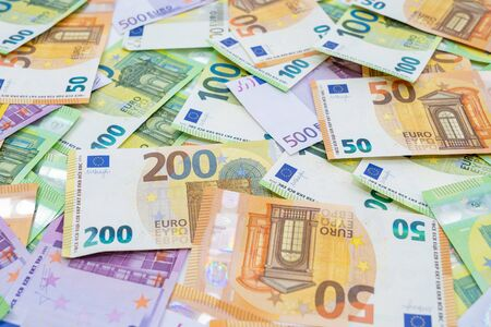 European currency lies on the table. Banknotes one hundred, two hundred, fifty, five hundred euros are scattered in a chaotic manner. Blank for design, background. Side view. 写真素材