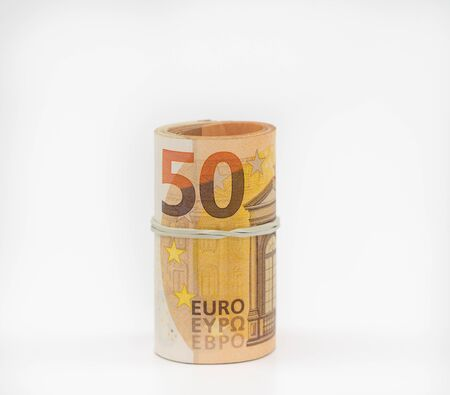 Banknotes fifty 50 euros in a roll with an elastic band. European currency to save. Close-up, white background. The concept of the safety of deposits and money. 写真素材