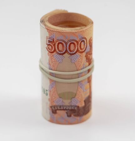 Banknotes five thousand rubles 5000 in a roll with an elastic band. Russian currency to save. Close-up, white background. The concept of the safety of deposits and money.