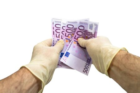 Two hands in white medical protective gloves are counting a bundle of bills with a face value of 500 five hundred euros. Isolated white background. Virus protection concept.
