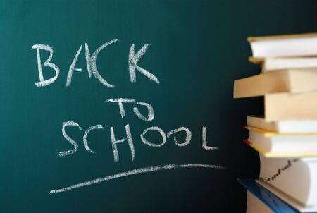 Message back to school written on the green chalkboard with some books on the right side. photo