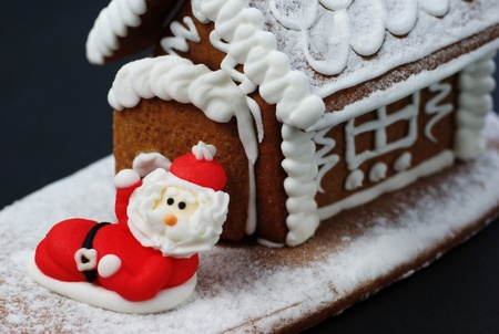 sugar paste: Santa Claus in front of gingerbread house.