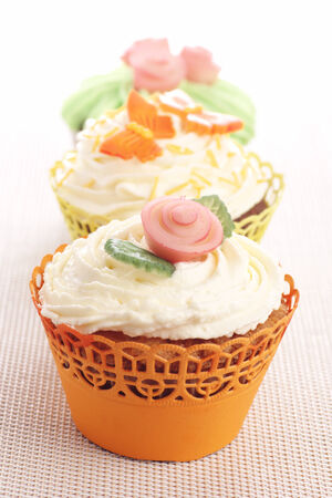 Three cupcakes decorated with marzipan decorations