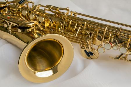 saxof�n: hermosa saxof�n de oro sobre fondo de seda blanca delicada Foto de archivo