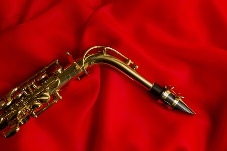 sheen: beautiful golden saxophone on delicate red silk background Stock Photo