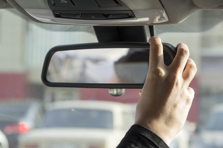 rearview: girl adjusts the rearview mirror Stock Photo