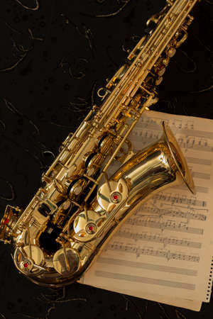 one sheet: Golden saxophone and music sheets on a black background