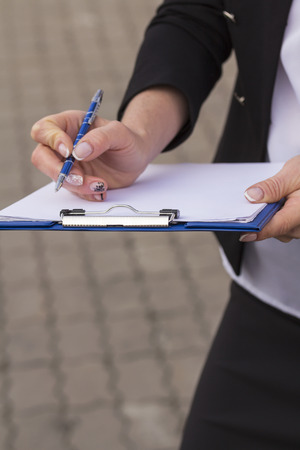 clip board: woman office worker holding a clip board with white paper