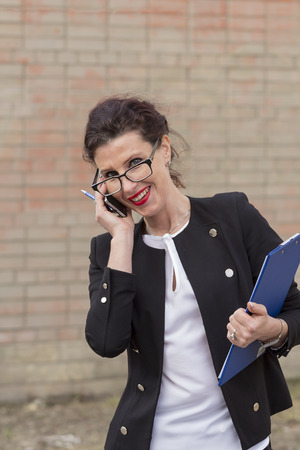 clip board: business woman talking on a mobile phone and holding a clip board Stock Photo