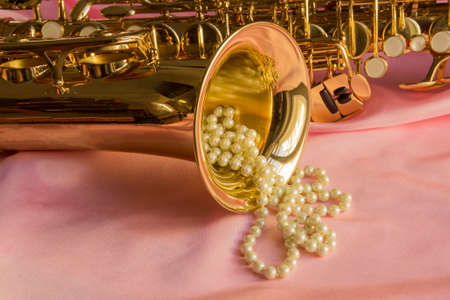 crystalline gold: Saxophone and Pearl necklace on Pink silk fabric soft Stock Photo