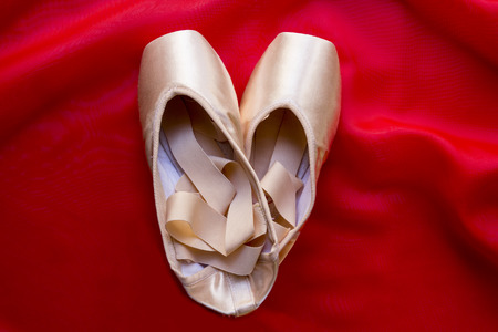 red silk: Ballet shoes on delicate red silk background