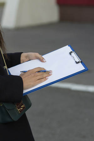 adult  body writing: the girl in the black coats in the hands of the clip board Stock Photo