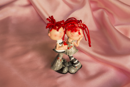 inseparable: souvenir statuette of a boy and a girl on a pink silk Stock Photo