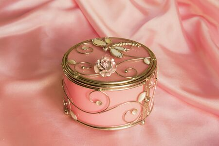 round brilliant: round decorative casket on a brilliant pink silk Stock Photo