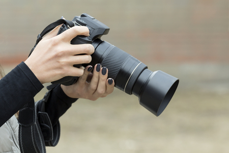 reflex camera: girl with beautiful manicure photographs on single-lens reflex camera