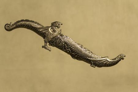 scheide: dekorativ geschnitzten Dolch mit den Leitern der Drachen in einem Mantel auf einem grauen Hintergrund