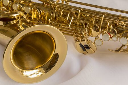 sheen: beautiful golden saxophone on delicate White silk background