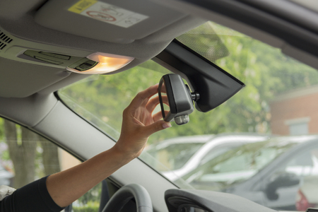mirro: girl adjusts the rear view mirror in a car Stock Photo