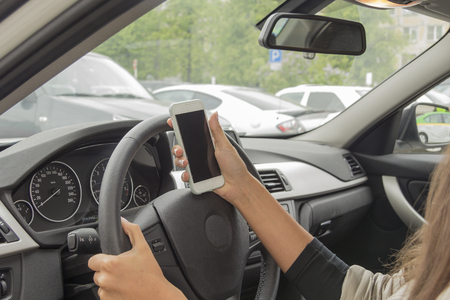 woman dialing phone number: girl with a mobile phone behind the wheel in the saloon car