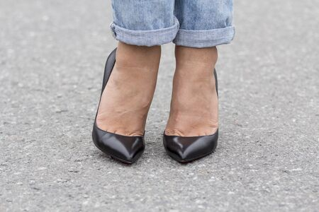 Feet girl in fashionable footwear, close-up on the road