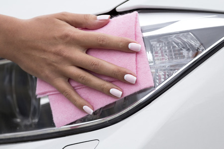 mote: Womans hand with a cloth to clean the headlights of the car