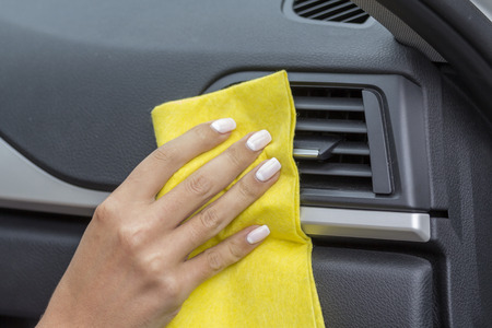 rag wheel: Hands girls wipe yellow cloth car interiors.