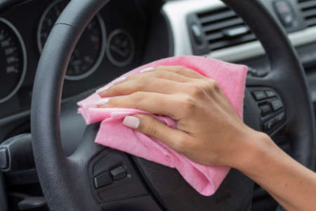 mote: Girls pink cloth wipe the hand wheel in the car.