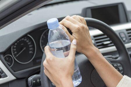 In de handen van het meisje een fles water in de auto.